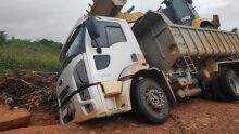 Caminhão que transportava retroescavadeira cai em cratera escondida pela enxurrada