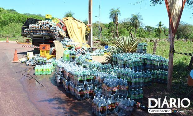 Caminhão carregado de refrigerante tomba e carga fica espalhada na pista