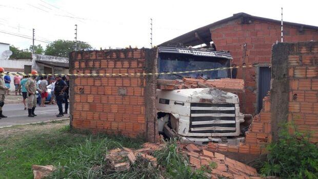 Motorista perde controle de carreta, bate contra muro e compromete estrutura de casa