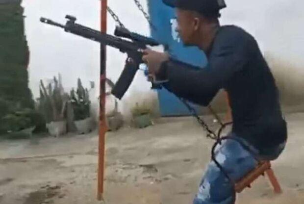 Bandido brinca de balanço enquanto segura fuzil