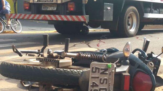 Motociclista bate em caminhão, vai parar debaixo do veículo e morre