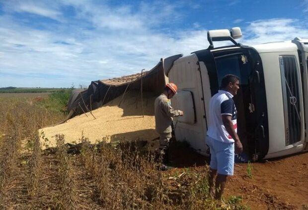 Caminhão cai em buraco, tomba e derrama 37 toneladas de farelo em estrada de chão