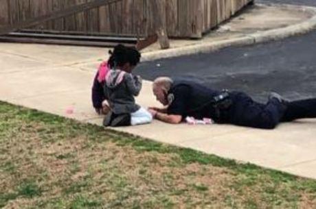 Policial deita no chão para brincar com crianças e bomba na internet