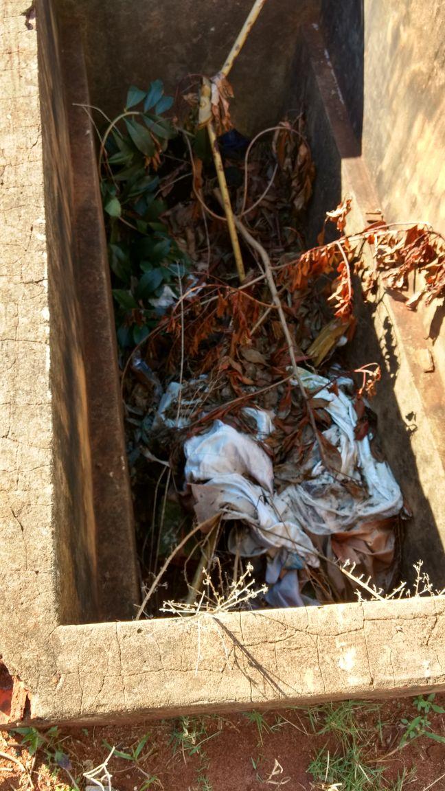 Túmulo aberto com pedaços de caixão, sapatos e lixo acumulado